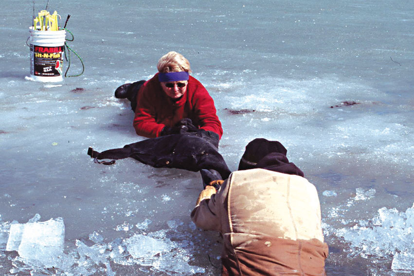 Woman pulling man who fell throught the ice out of the water