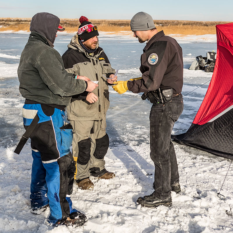 Department district game warden, checks fishing licenses