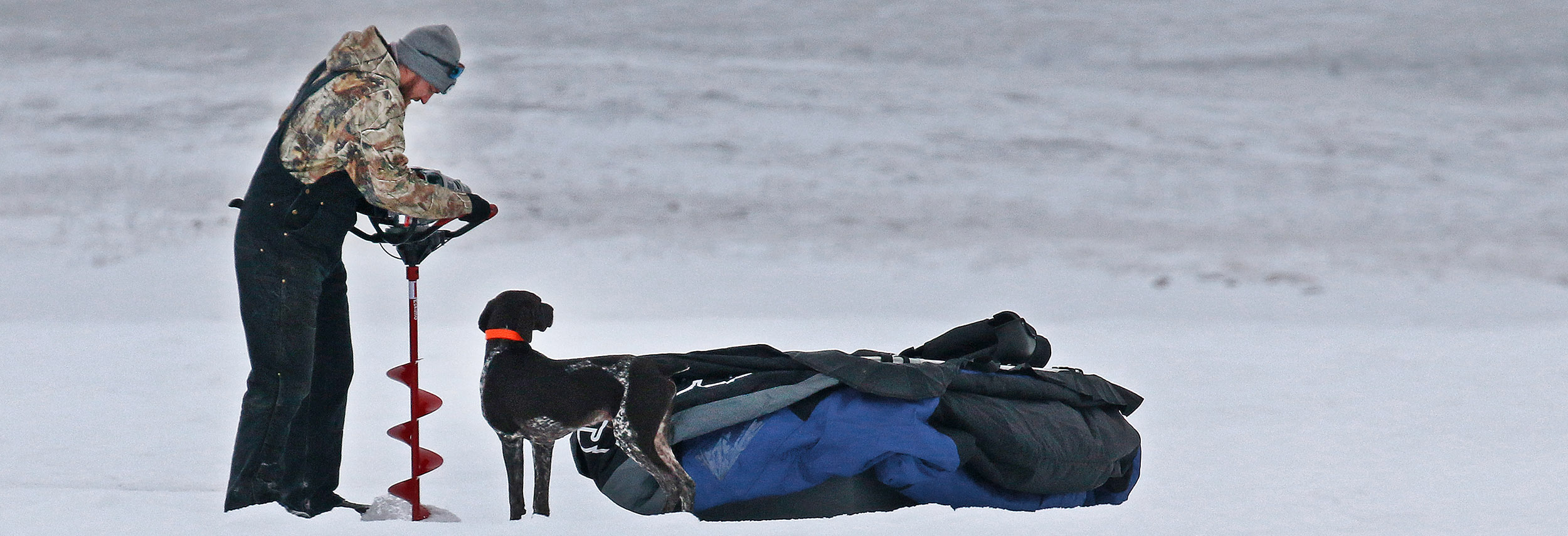 Man drilling ice hole with dog standing by