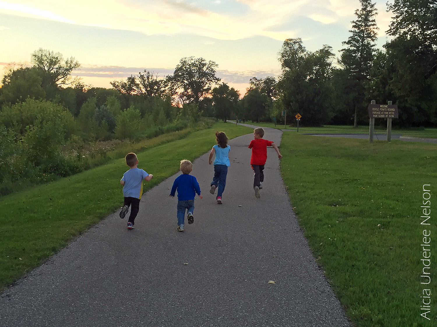 Kids running along a path in the Grand Forks Greenway