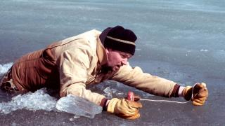 Man using picks to get out of hole in ice