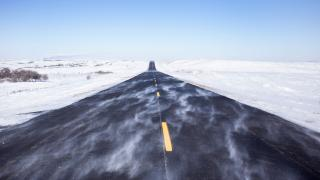 Snow blowing over road